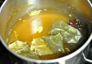 Green tea bags added to chai spices and water in saucepan