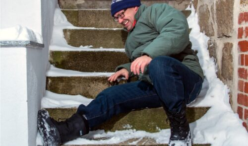 man slipping on icy front porch stairs