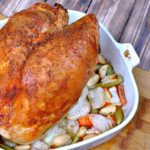 Delicious roasted turkey breast in a pan over veggies