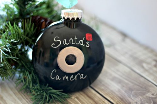 Finished Santa Cam ornament on a table next to an artificial Christmas tree branch