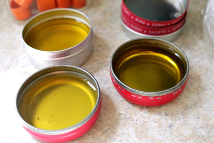 Melted sinus relief body balm poured into red metal tins