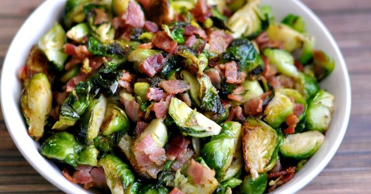 Bowl of delicious bacon and brussels sprouts on a wood table