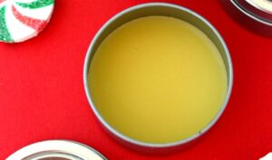 Homemade peppermint lip balm ready to use on a red table