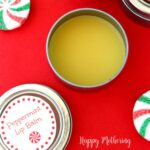 Homemade peppermint lip balm tin on counter with printed label for gifting