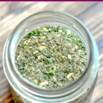 Pint sized mason jar on wood table filled with homemade ranch seasoning