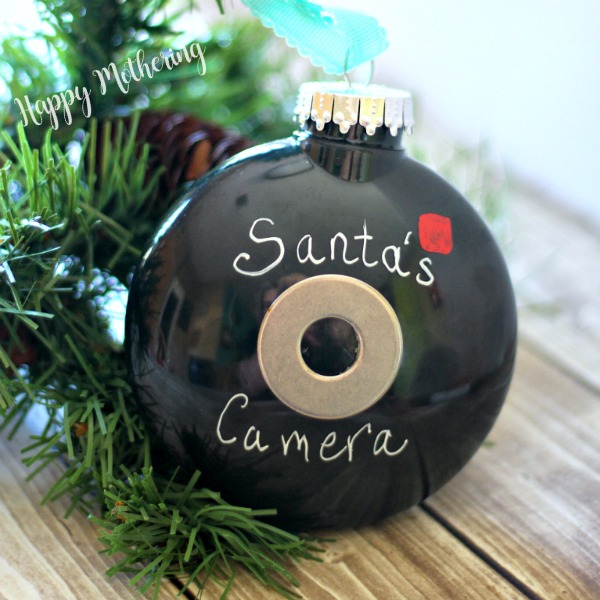 DIY Santa Cam ornament with artificial Christmas tree branches on a wood table