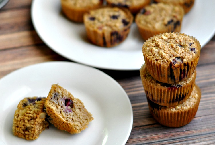 Stack of baked oatmeal blueberry muffins with one sliced in half so you can see the inside