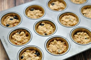 Baked oatmeal blueberry muffin batter in a muffin pan