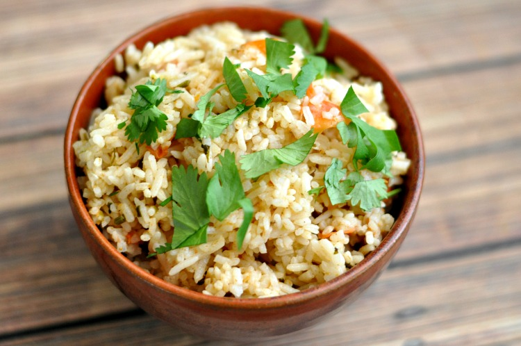 Bowl of Spanish Rice prepared in the Instant Pot and topped with chopped cilantro on a wood table