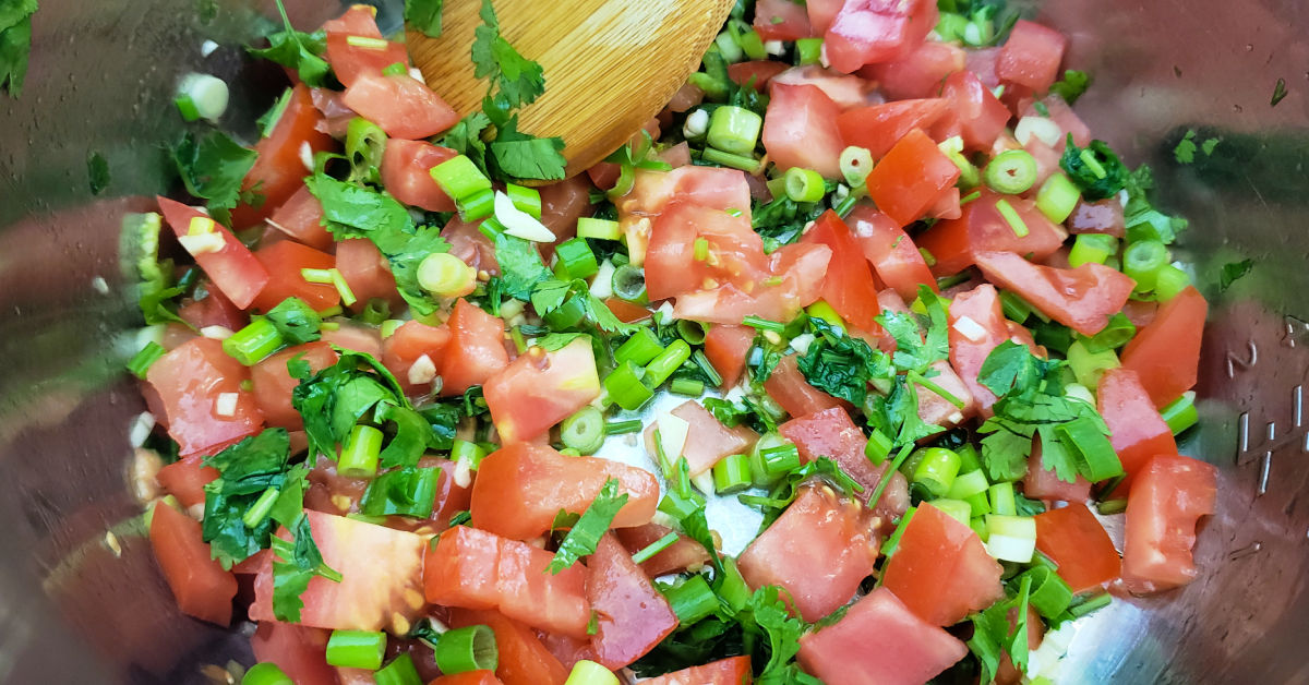 Tomatoes, cilantro, green onions and garlic being sauteed in the Instant Pot inner pan.