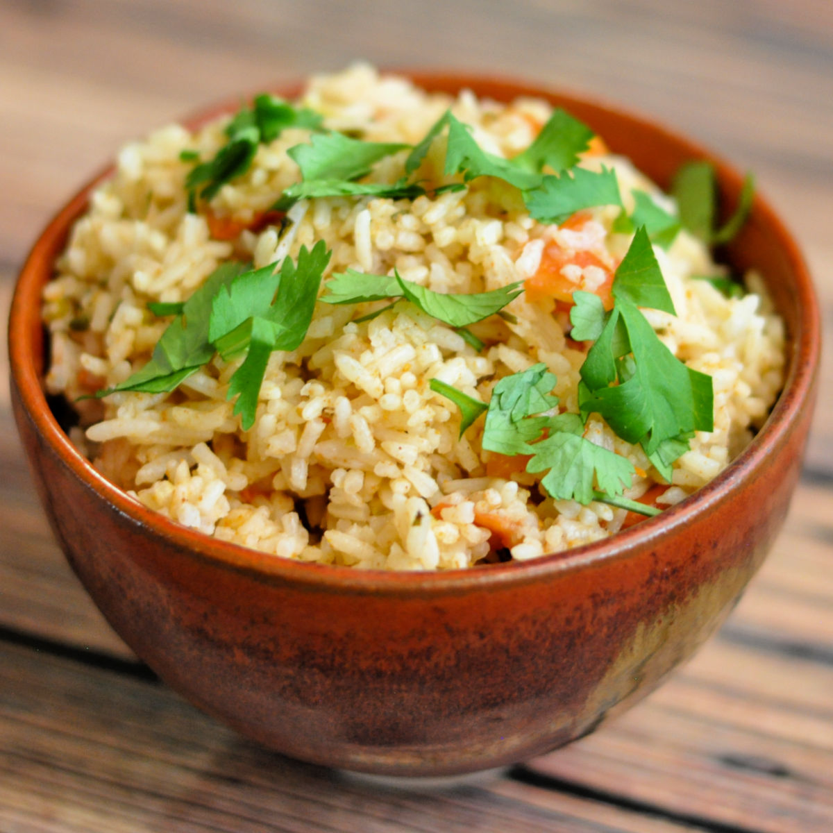 Spanish rice garnished with cilantro in a red ceramic bowl.