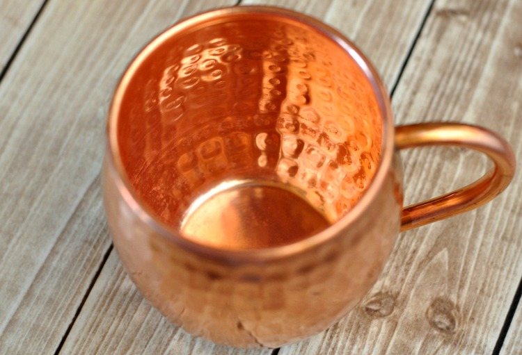 Clean copper mug on a light wood table