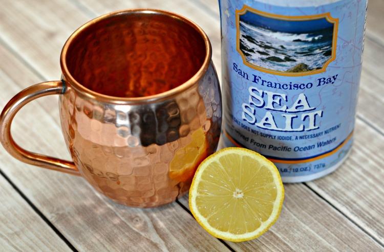Copper mug with half a lemon and sea salt on a table