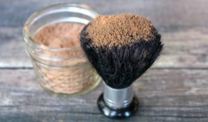 Close up of DIY bronzer on large makeup brush with jar of more bronzer in background on wood table
