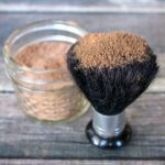 Close up of large makeup brush dipped in homemade bronzer in a glass jelly jar on a wood table