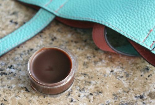 Chocolate lip balm on a granite counter with a blue purse