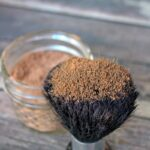 Homemade bronzer powder in a glass jar with a makeup brush that has been dipped in it to show the color