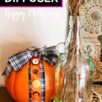 DIY reed diffuser on wood table with decorative pumpkin and doily