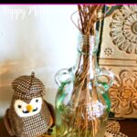 Homemade reed diffuser on doily on table next to stuffed owl
