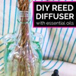 DIY reed diffuser with two essential oil bottles on blue and white striped towel as background