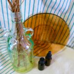 Reed diffuser, two essential oil bottles and a brown glass plate displayed on a white and blue striped kitchen towel