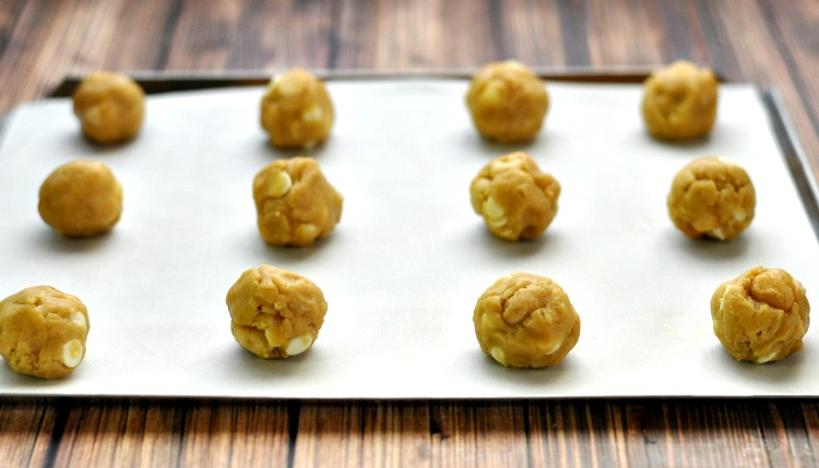 White chocolate macadamia nut cookie balls on baking sheet ready for the oven