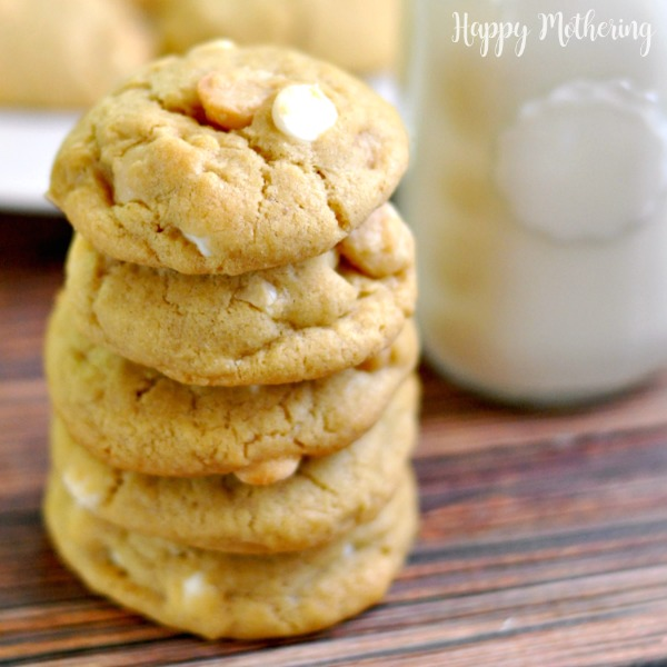 Stack of homemade white chocolate macadamia nut cookies on a table with milk