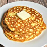 Close up of stack of low carb pancakes on a white plate with a pat of butter