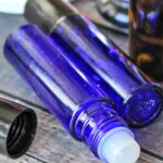 Two blue roller bottles with homemade lip gloss on a brown table with a bottle of essential oil