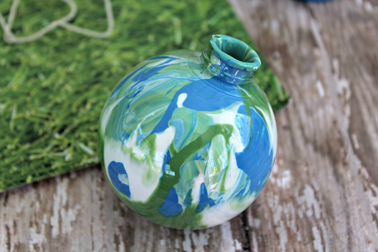 Green, white and blue paint swirled around inside of a clear fillable globe ornament
