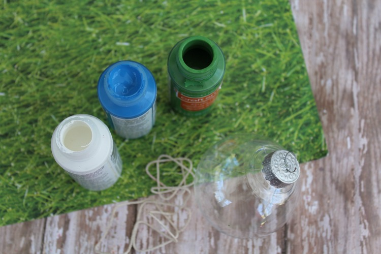 Craft paint, clear fillable Christmas ornament and twine on a table