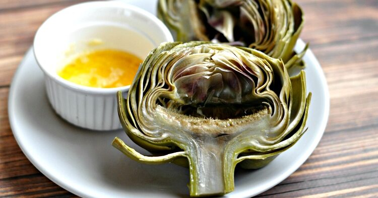 Instant Pot Artichokes on a white plate with garlic dipping butter