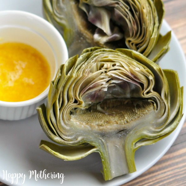 Close up of Instant Pot Artichokes on a white plate with butter