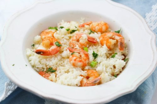 Shrimp scampi over white rice in a white ceramic bowl