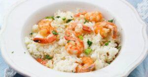 Shrimp scampi over white rice in a white ceramic bowl