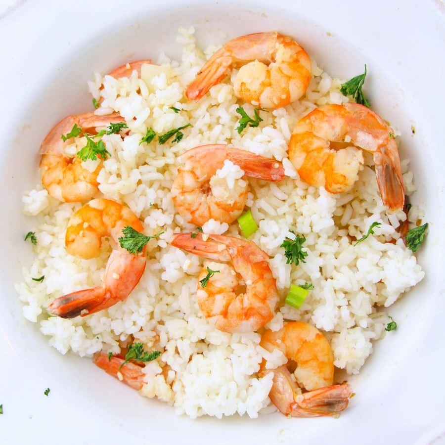 Overhead view of white bowl of shrimp scampi over white rice with a parsley garnish, prepared in an Instant Pot