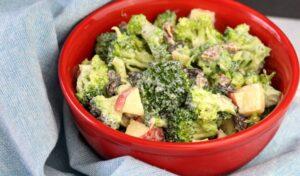 Red bowl of homemade broccoli salad on light blue towel