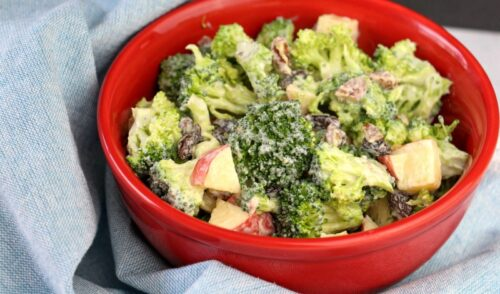 Red bowl of homemade broccoli salad on light blue towel
