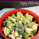 Red bowl of broccoli salad with a creamy homemade dressing, set on a light blue towel
