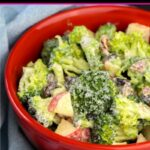 Red bowl filled with homemade broccoli salad with apple chunks