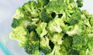 Chopped broccoli in a glass mixing bowl