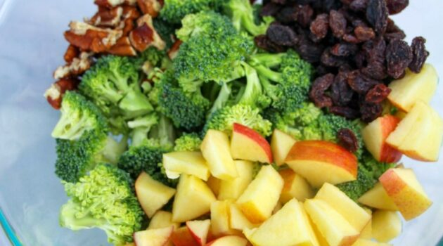 Chopped broccoli, apples, raisins and pecans in a glass mixing bowl