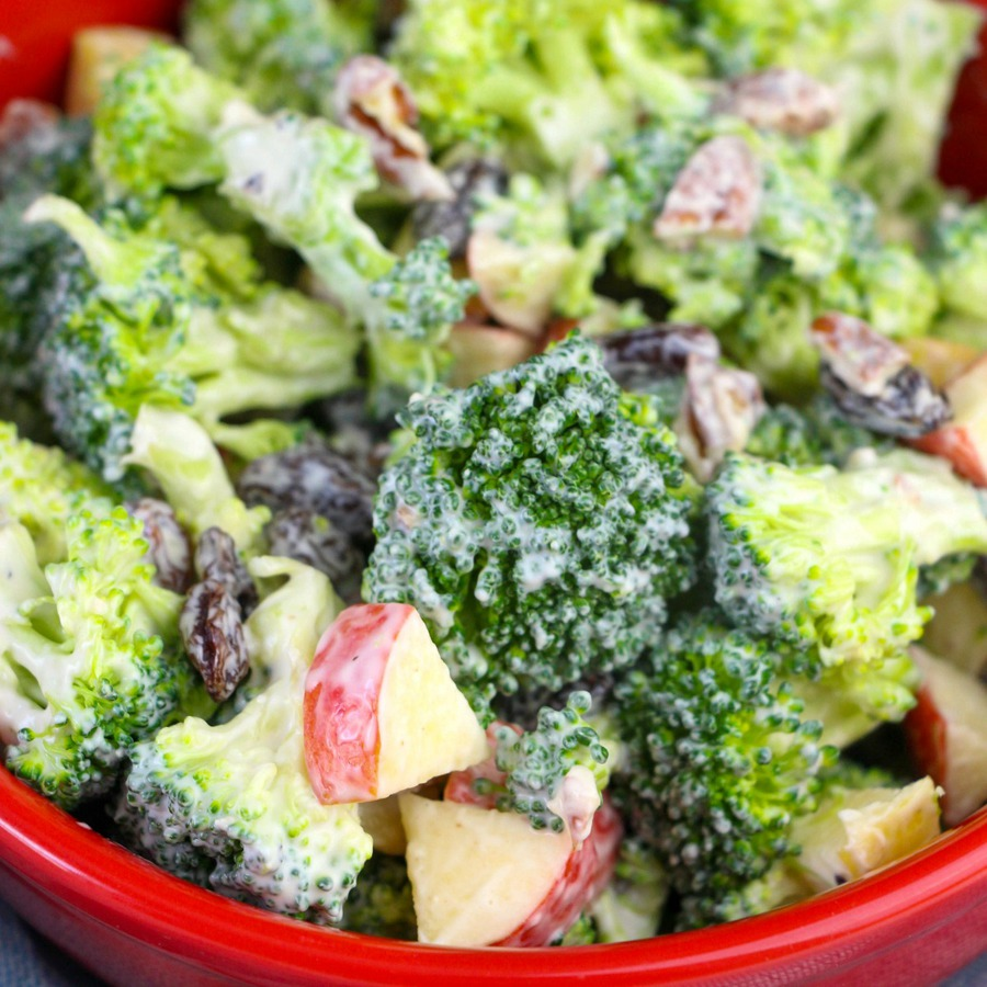 Super close up view of chunky broccoli salad with apple chunks, raisins and creamy dressing