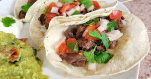 Close up of inside of homemade carne asada taco topped with pico de gallo in a corn tortilla