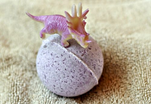 Toy triceratops on top of a toy surprise bath bomb