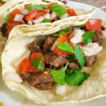 Close up carne asada street tacos that were prepared in an Instant Pot, topped with homemade pico de gallo