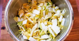 Napa cabbage after being massaged with sea salt in a metal mixing bowl.