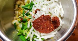 Napa cabbage, green onions, daikon radish and kimchi chili paste in mixing bowl.