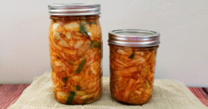 Sealed mason jars of kimchi fermenting on a kitchen towel.
