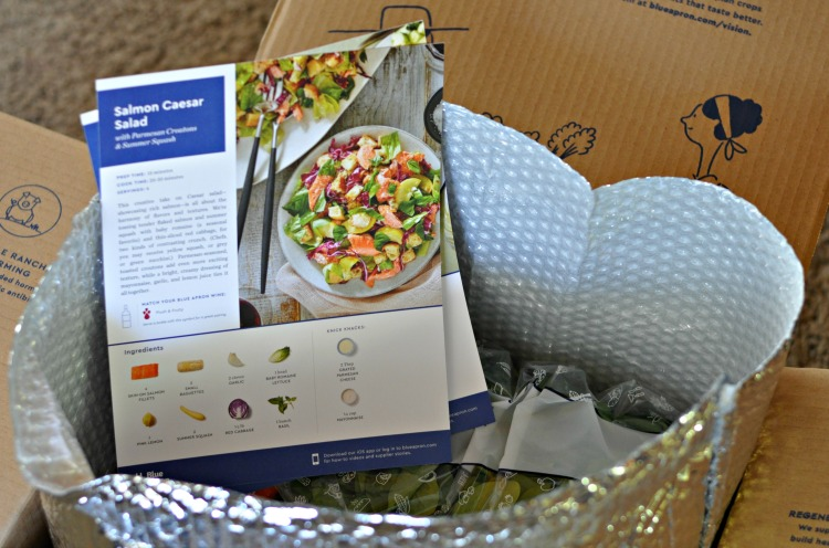 Blue Apron meal kit box opened showing recipe cards and fresh ingredients